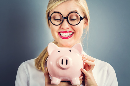 Young blonde woman with a piggy bank